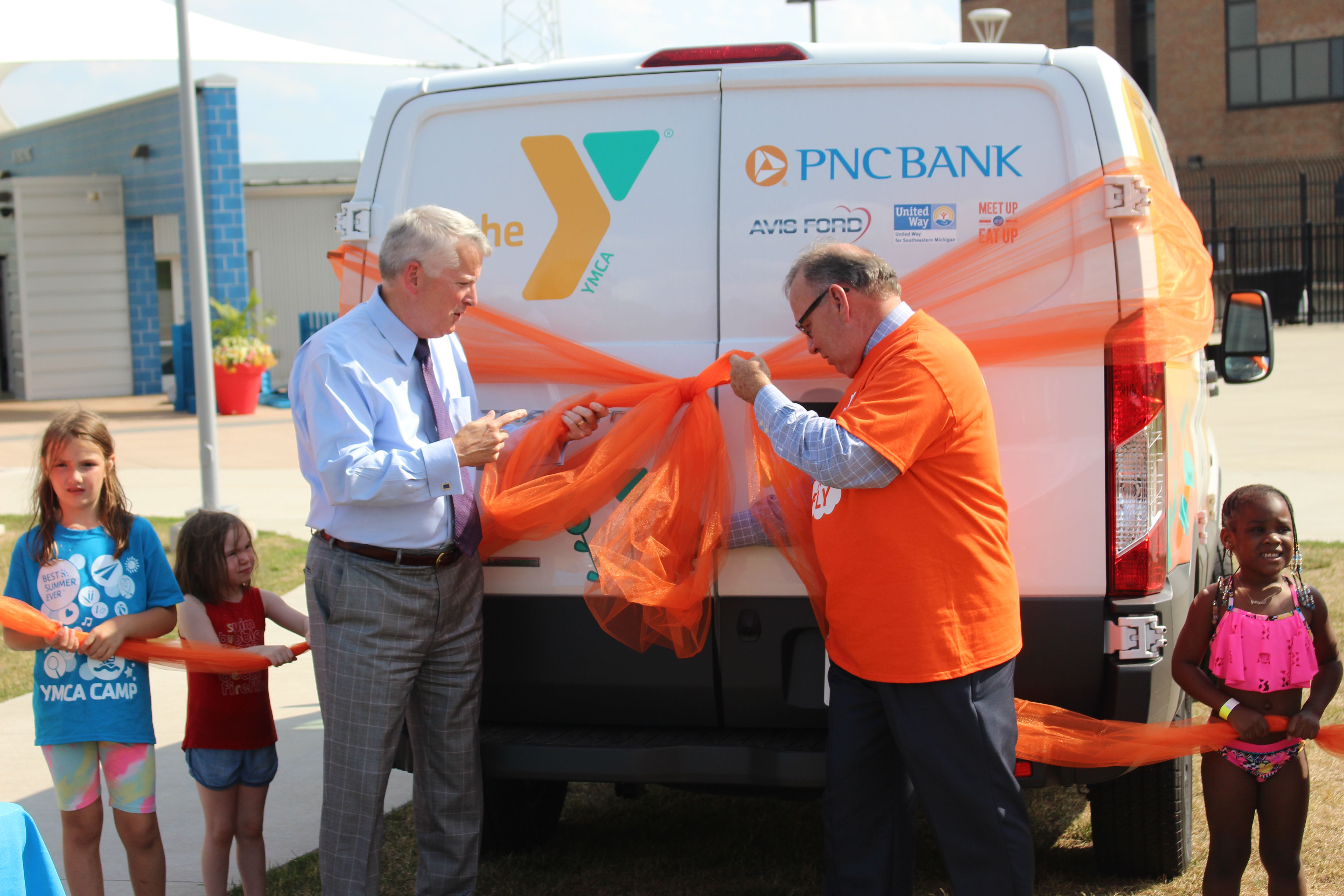 Ric Devore (left) and Scott Landry (right) cutting the ribbon to the new Y on the Fly van in Detroit.